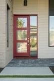 Porte extérieure rouge moderne fermée d'une maison Photos libres de droits