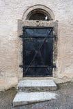 Porte noire de fer avec dans le bâtiment en pierre blanc Images stock