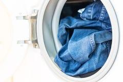 Porte ouverte dans le mashine de lavage avec des jeans à l'intérieur Photographie stock