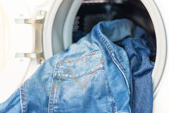 Porte ouverte dans le mashine de lavage avec des jeans à l'intérieur Image stock