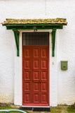 Porte rouge avec un toit Photographie stock
