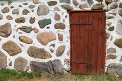 Porte rouge dans le mur en pierre de rocher Photographie stock