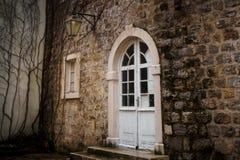 Porte semi-circulaire blanche avec le verre dans le mur en pierre de la vieille ville dans Budva, Monténégro image stock