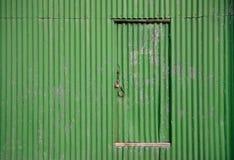 Porte sur un vieux hangar de vert Photos stock