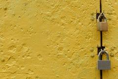Porte texturisée en métal peinte avec la peinture jaune avec deux serrures en métal photographie stock