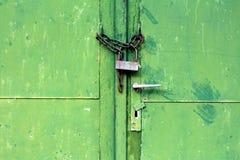 Porte verdi del metallo con pittura incrinata e la maniglia di porta dilapidata chiuse a chiave con la catena arrugginita ed il v fotografia stock libera da diritti