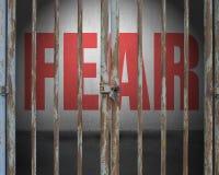Porte verrouillée avec crainte rouge de mot sur le mur en béton Photos stock