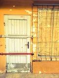 Porte verrouillée et fenêtre couverte d'une boutique abandonnée Images stock