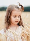Porteait,夏天麦田的逗人喜爱的小女孩 有麦子花束的一个孩子在他的手上 库存照片