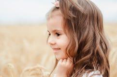 Porteait,夏天麦田的逗人喜爱的小女孩 有麦子花束的一个孩子在他的手上 免版税库存图片