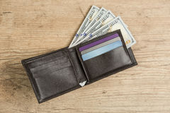 Portefeuille avec 100 billets d'un dollar sur une table en bois Image libre de droits
