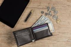 Portefeuille avec 100 billets d'un dollar sur une table en bois Images libres de droits