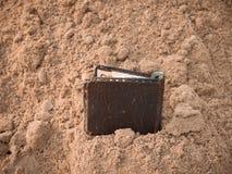 Portefeuille avec l'argent sur le sable photographie stock libre de droits