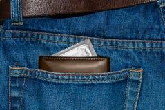 Portefeuille dans une poche de blues-jean avec le préservatif argenté Images libres de droits
