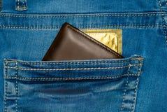 Portefeuille dans une poche de blues-jean avec un préservatif d'or Images libres de droits