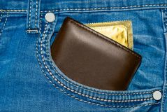 Portefeuille dans une poche de blues-jean avec un préservatif d'or Image stock