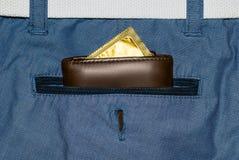 Portefeuille dans une poche de blues-jean avec un préservatif d'or Photo libre de droits