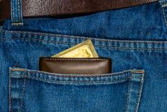 Portefeuille dans une poche de blues-jean avec un préservatif d'or Photos libres de droits