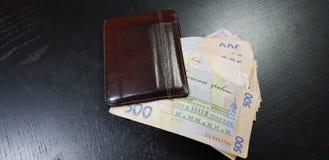 Portefeuille en cuir de Brown plein avec cinq cents billets de banque de hryvnia photos stock