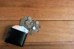 Portefeuille en cuir noir avec des billets de banque et des pièces de monnaie d'argent photographie stock libre de droits