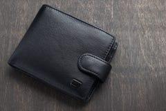 Portefeuille en cuir noir sur un fond en bois Photos libres de droits