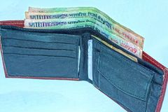 Portefeuille en cuir ouvert avec 100 roupies de billets de banque indiens sur un fond blanc images libres de droits