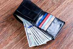 Portefeuille noir en cuir avec des dollars et des cartes de crédit photographie stock libre de droits