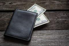Portefeuille noir et dollar américain à bord Photographie stock libre de droits