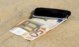 Portefeuille sur le sable. Images libres de droits