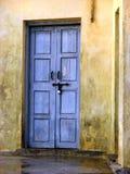 Portello blu in pareti gialle Fotografia Stock