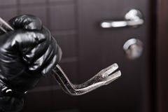 Portello di apertura della rottura del bastone a leva della holding della mano dello scassinatore fotografie stock