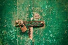 Portello Locked Vecchio lucchetto arrugginito chiuso su una porta di legno afflitta fotografia stock