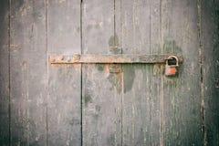 Portello Locked Vecchio lucchetto arrugginito chiuso su una porta di legno stagionata fotografie stock