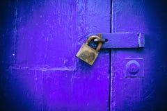 Portello Locked Vecchio lucchetto arrugginito chiuso su una vecchia porta di legno blu fotografia stock