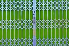 Portello scorrevole della griglia verde del metallo con la serratura di cuscinetto Immagini Stock
