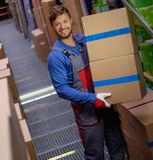 Porter carrying boxes. In a warehouse stock photo