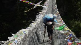 Porter is carrying a cargo in the Himalayas. Porter with a cargo goes on a suspension bridge. Track to the base camp of Everest in the Himalayas. Sagarmatha stock video footage