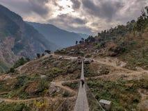 Porter crossing suspension bridge in remote village of Nepal. stock image