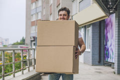 Porter, the man with cardboard boxes in the hands of a strong, d Stock Photos