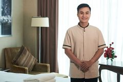 Porter. Portrait of smiling Vietnamese porter in hotel room royalty free stock photography