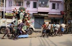 Porter pulling Durga Idol Stock Photography