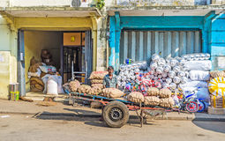 The porter at the warehouse. COLOMBO, SRI LANKA - DECEMBER 6, 2016: The porter sits at the warehouse in Pettah, behind the large trolley, loaded with potato bags Royalty Free Stock Images