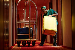 Porter at work. Hotel servant taking out suitcase with baggage from hotel room Royalty Free Stock Photo
