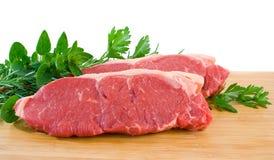 Porterhouse Steak. Two raw porterhouse steaks on a wooden chopping board with herbs Stock Photos
