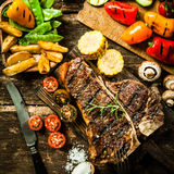 Porterhouse steak with assorted roast vegetables. View from above of a delicious grilled porterhouse steak with assorted roast vegetables including tomato Stock Photo