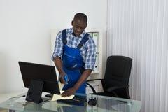 Portero Cleaning Glass Desk con el paño en oficina Fotografía de archivo