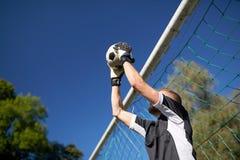 Portero con la bola en la meta del fútbol en campo imágenes de archivo libres de regalías