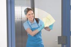 Portero de sexo femenino Cleaning Glass Imagenes de archivo