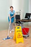 Portero de sexo femenino Cleaning Hardwood Floor en oficina Fotografía de archivo libre de regalías
