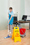Portero de sexo femenino Cleaning Hardwood Floor en oficina Imagen de archivo libre de regalías